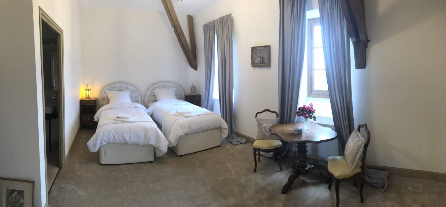 One of Chateau Fengari's bedrooms, with twin beds and plush carpet
