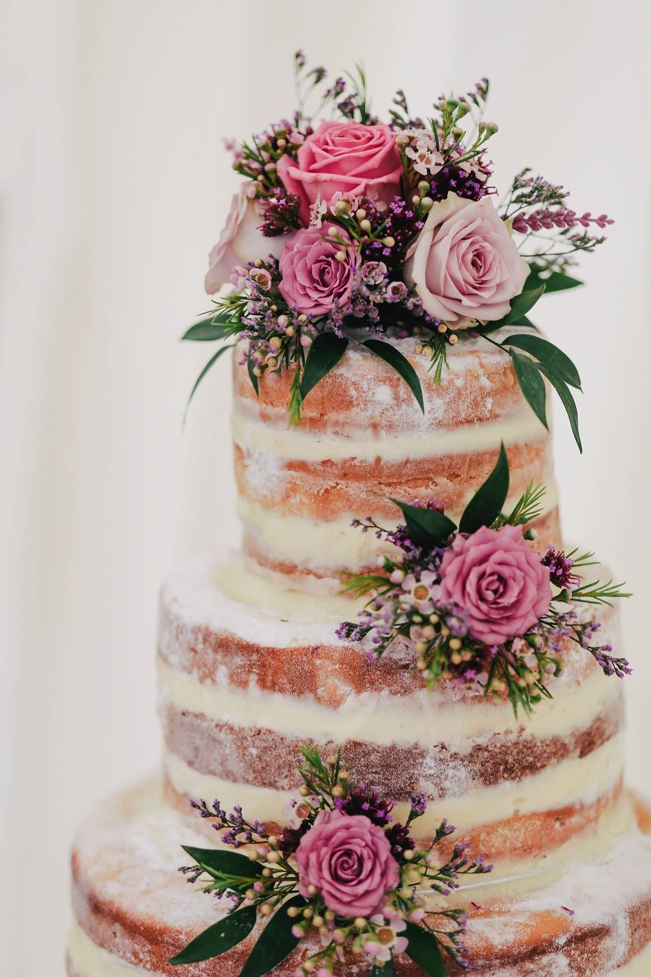 A naked wedding cake with flowers